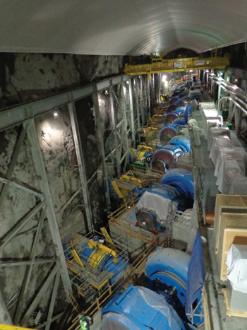 The nearly finished underground powerhouse is shown above, 144 m in length, 27 m in height, and 17 meters in width, complete with nine 22-MW horizontal Francis turbines.