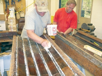 Workers are seen here assembling bearing shoes by adding blocks of lignum vitae wood to the frame.