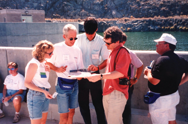 Marla Barnes, then with HCI Publications, and other attendees look over documentation on a plant tour at the first HydroVision International in 1994.